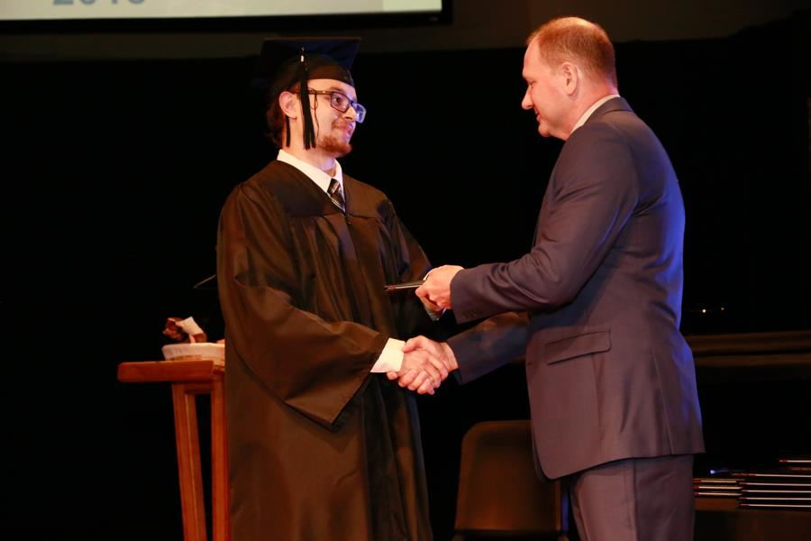 graduate receiving diploma from Board member Paul Harrell